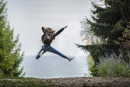body-adventure-girl-jumping-backpack