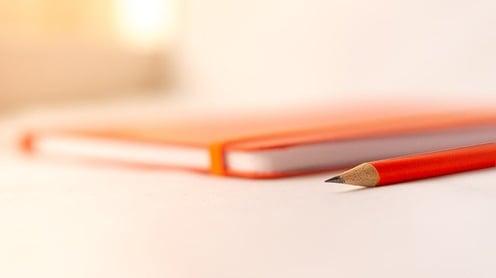 feature_orange_notebook_pencil_college_essay_topics